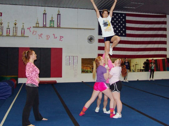 Grace Gottwalt is lifted by fellow cheer squad members while Wendy Guilliams watches during practice at Flip-N-Out Gymnastics in Kimbolton.