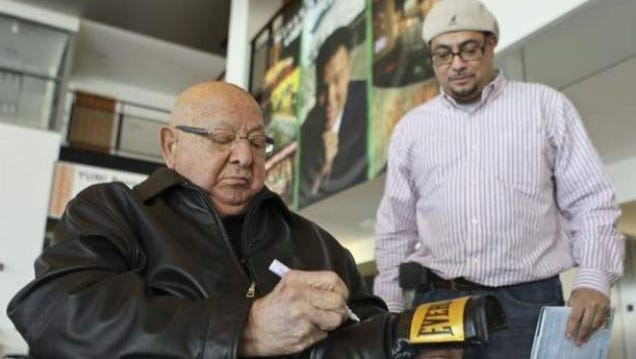 Angelo Dundee, 90, signs a boxing glove while fan Geraldo Reyes, Jr. watches at the Muhammad Ali Center.
