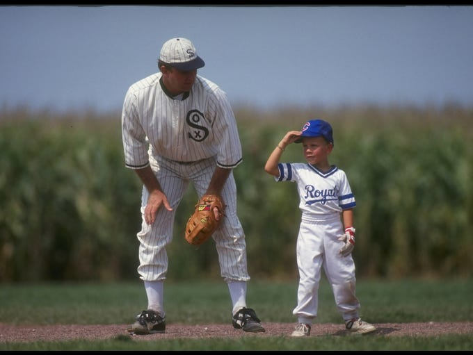"A ""ghost player"" recreating the role of Chicago White Sox legend Shoeless Joe Jackson plays ball with a young tourist at the baseball field created for the motion picture 'Field of Dreams' on August 25, 1991 in Dyersville, Iowa. Rita and Al Ameskamp who, with Don and Becky Lansing, co-own the site have turned the cornfields and baseball diamond into a summertime tourist attraction, including ""ghost player"" reenactments."