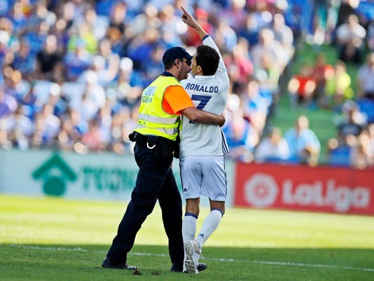 A security guard grabs a fan wearing a Cristiano Ronaldo shirt after he invaded the pitch during a Spanish La Liga soccer match between Getafe and Real Madrid at the Coliseum Alfonso Perez in Getafe, Spain, Saturday, Oct. 14, 2017. (AP Photo/Paul White)