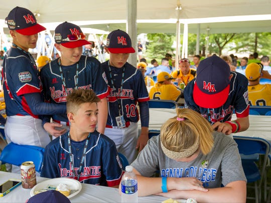 Brody Raleigh, seated left watches as his Maine-Endwell teammates autograph Pennsylvania College of Technology student Cassandra Henderson's shirt, Wednesday afternoon, at a picnic on the campus for all 16 teams teams prior to the Grand Slam Parade in Willamsport.
