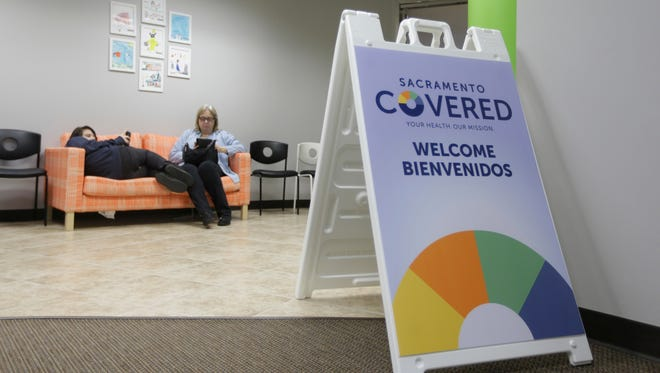 In this Feb. 12, 2015 file photo Laura San Nicolas, right, and her daughter Geena, wait to meet with an enrollment counselor to sign up for health insurance at Sacramento Covered in Sacramento, Calif.