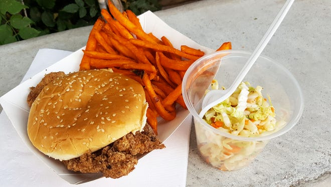 The hot chicken sandwich with sweet potato fries ($8) and a side of vinegar-based coleslaw. The sandwich is coated with seasoning, and topped with red onion and homemade jumbo fresh pickles.