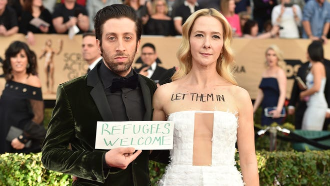 Simon Helberg, left, and Jocelyn Towne display protest signs against the U.S. policy of temporarily barring refugees and citizens of seven predominantly Muslim countries, at the 23rd annual Screen Actors Guild Awards at the Shrine Auditorium & Expo Hall on Sunday, Jan. 29, 2017, in Los Angeles.