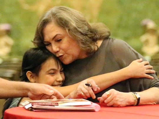 Emery Salgado, 9, reaches to hug actress Kathleen Turner after getting an autograph from her Saturday at the El Paso Community Foundation in downtown El Paso.