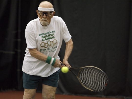 Lee Stadem returns a serve during a doubles game at