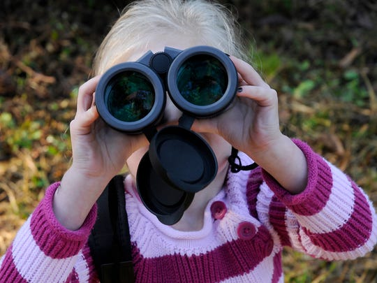File Photo - Lynzi Stone, 4, uses binoculars to get closer to some of the wildlife on a nature hike during a celebration at the Red River National Wildlife Refuge Saturday morning.