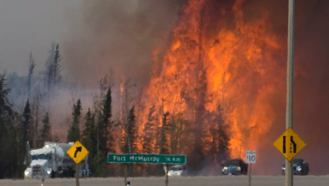 Heat waves are seen as cars and trucks try and get past a wildfire 16 kilometers south of Fort McMurray, Alberta, on Highway 63, on May 6, 2016.