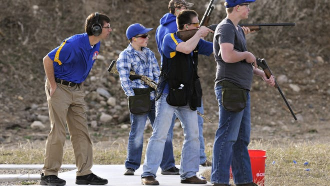 Members of the Kimball High School trapshooting team take turns shooting during practice as coach Rob Kuechle watches Wednesday, April 15, 2015, at the Kimball Rod & Gun Club.
