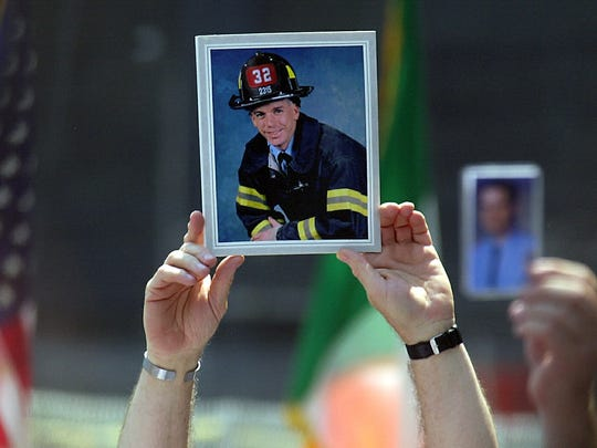Family members hold up photos of loved ones lost during the terrorist attacks on the World Trade Center at a service  marking the final recovery efforts at Ground Zero on June 2, 2002.