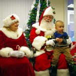 Santa and Mrs. Claus (Jim and Jeannette Lockwood) visit with 2-year-old Andrew Lengyel at the village of Webster offices during Webster's White Christmas in the Village celebration on Dec. 6.