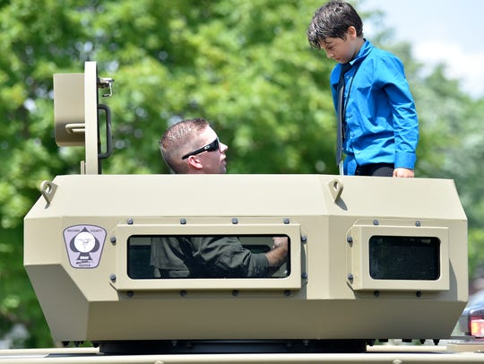 SWAT officer Chris Bennett, left, talks with Isaiah as they stand in the observation turret of a Bearcat armored vehicle.