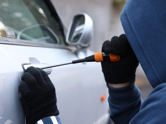 Someone using a tool to break into a car