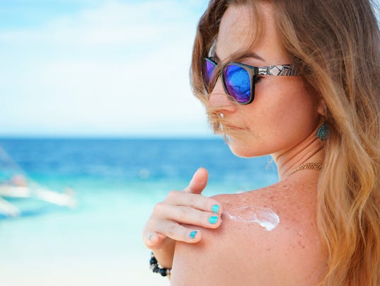 young woman with sunglasses applyng sun protector cream at her