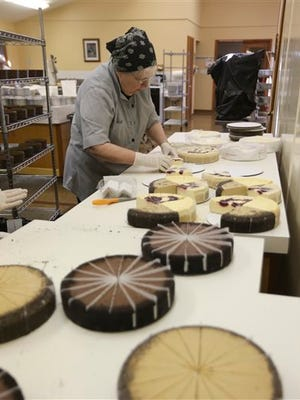 In this Thursday, July 16, 2015 photo, Sister Rebecca handles frozen cheesecake that will be packaged into sampler packs at New Skete Kitchens in Cambridge, N.Y. The nuns of New Skete lead a cloistered life marked by prayer, contemplation and baking cheesecakes, lot's of cheesecake. The small group of fiercely self-reliant nuns in upstate New York have long sold cheesecakes online, continuing a centuries-old tradition of monastic orders producing fine foods to pay expenses. (AP Photo/Mike Groll)