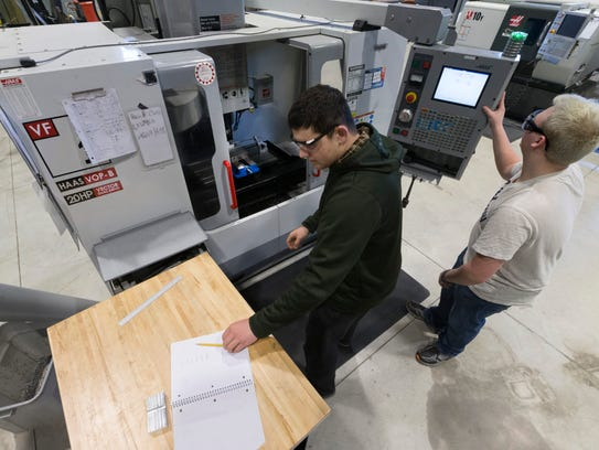 CNC machinist student Andrew Fairchild (right) assists