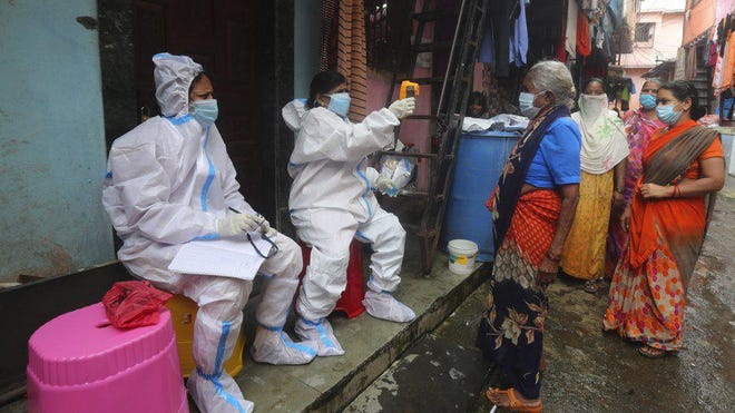 Health workers screen people for COVID-19 symptoms in Dharavi, one of Asia's biggest slums, in Mumbai, India, Tuesday, Aug. 11, 2020. India has the third-highest coronavirus caseload in the world after the United States and Brazil.