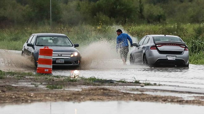 A man leaves his car after it stalled in floodwater at East Slaughter Lane and Vertex Boulevard after heavy rainfall in Austin on Friday morning. Parts of Travis County saw between 3 and 4 inches of rainfall.