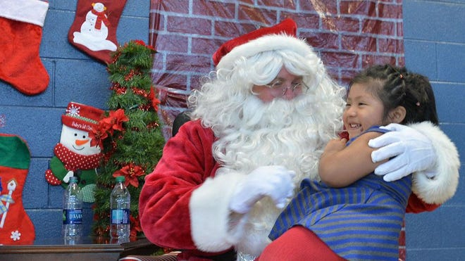 In this 2016 photo, Majeair Castanon visits with Santa during the Bounty of Bethlehem Christmas Day dinner in the Immaculata Catholic School gym. For more than three decades, Bounty of Bethlehem has offered a classic family dinner on Christmas Day to people in the community who may not have their own family to spend it with.