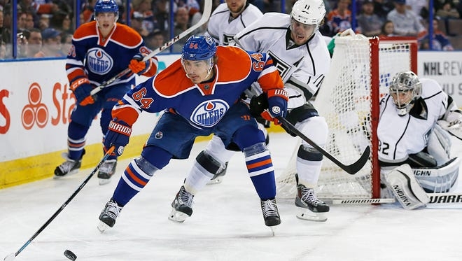 Edmonton Oilers forward Nail Yakupov (64) is chased around the Los Angeles Kings net by forward Anze Kopitar (11) during the second period at Rexall Place.