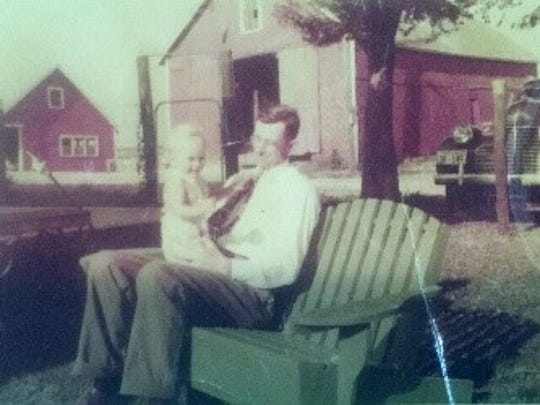 John Kruse holds his son Loren on the front lawn of