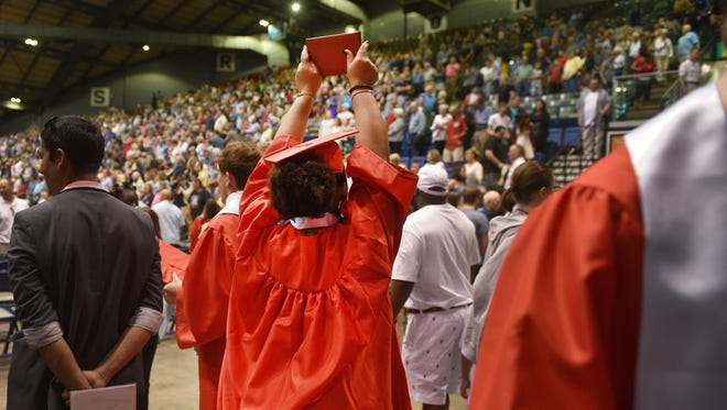 A Lincoln High School student holds up her diploma while trying to find her family after graduation, Sunday, June 3, at the Sioux Falls Arena.