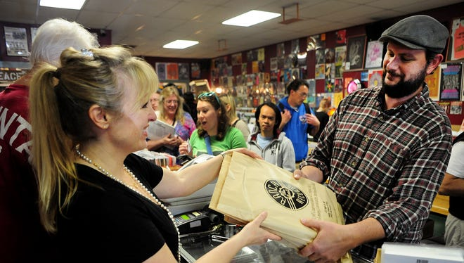 Sean Fallin, of Keizer, picks up his purchase from Lori Close, co-owner of Ranch Records, on Saturday at the Salem store. Sean Fallin, of Keizer, picks up his purchase from Lori Close, co-owner of Ranch Records, during Record Store Day, on Saturday, April 18, 2015, in Salem.