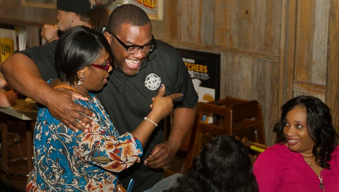 Curt Sheard, creator and founder of Big Boi's BBQ, celebrates with family and friends after learning he won an episode of A&E's Rooster & Butch on Wednesday at a watch party at Miller's Ale House in Fort Myers. Sheard's BBQ sauce collection earned him the victory.