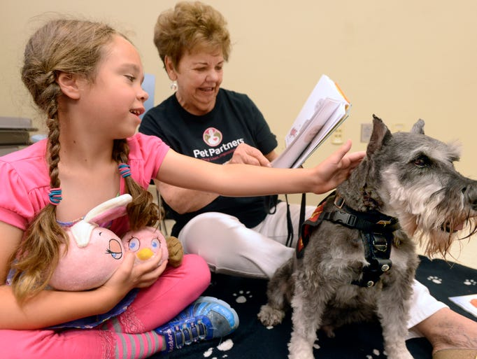 Chancey Cogley, 6, pets R.E.A.D. therapy dog Dreamer, a schnauser owned by instructor Joan Ziel, center, on Saturday morning at the Tryon branch library on Langley Ave. The Reading Education Assistance Dogs were provided by Pet Partners Therapy Animal Teams. R.E.A.D. dogs are trained to listen in a non-judgmental manner while your child reads to them. Cabo, a basset hound, and Angel, a sheltie owned by Tim and Karen Prichard, were also on hand to assist the kids with their reading.