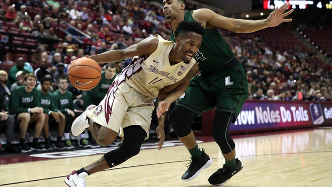 FSU's Braian Angola drives the baseline past Loyola of Marylandâs Chuck Champion during their game at the Tucker Civic Center last week.