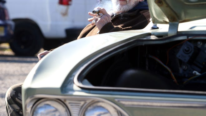 Ron Stephensen enjoys a cigar next to his 1967 Corvair. The Barnegat-Waretown Chamber of Commerce held a Hot Rods & Heroes Car Show event at Fred Watts Gazebo Park in  Barnegat, New Jersey. Saturday, November 11, 2017. David Gard /Correspondent