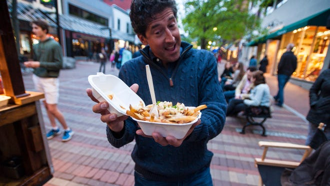 A happy customer with an offering from the Maudite Poutine food cart on Church Street in Burlington on Friday, June 2, 2017.