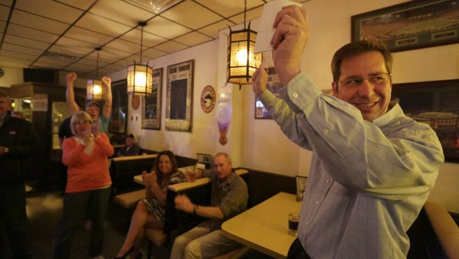 Menasha Mayor Don Merkes celebrates with supporters Tuesday at Club Tavern as election results come in. He was re-elected to a third term.