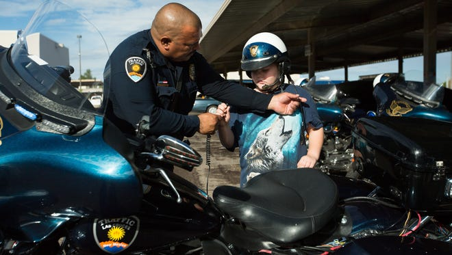 Las Cruces Police Officer David Gonzalez, left, helps Gabriel Hoover, 8, attach a radio to a helmet Wednesday, August 3, 2016, during Gabriel's tour of the LCPD headquarters. The department gave Gabriel, 8, who is autistic, a tour of their facilities and also named him an honorary officer.