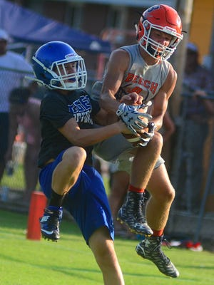 Beech High junior Ty Dean rips the ball away from Macon County freshman Isaac Belton for an interception during Trousdale County's 7-on-7 workouts on Tuesday afternoon.