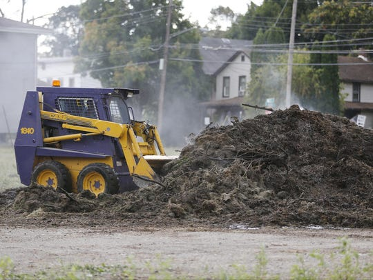 An Elmira College excavator levels out a mulch pile