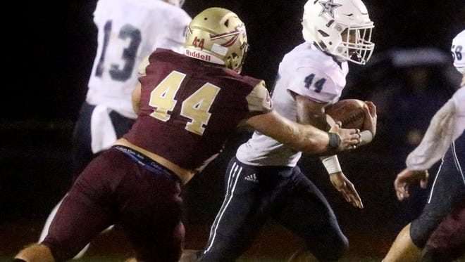 Siegel's Lelan Wihoite (44) runs the ball as Riverdale's Austin Rowland (44) moves in for the tackle during the game, on Friday, Sept. 1, 2017, at Riverdale.