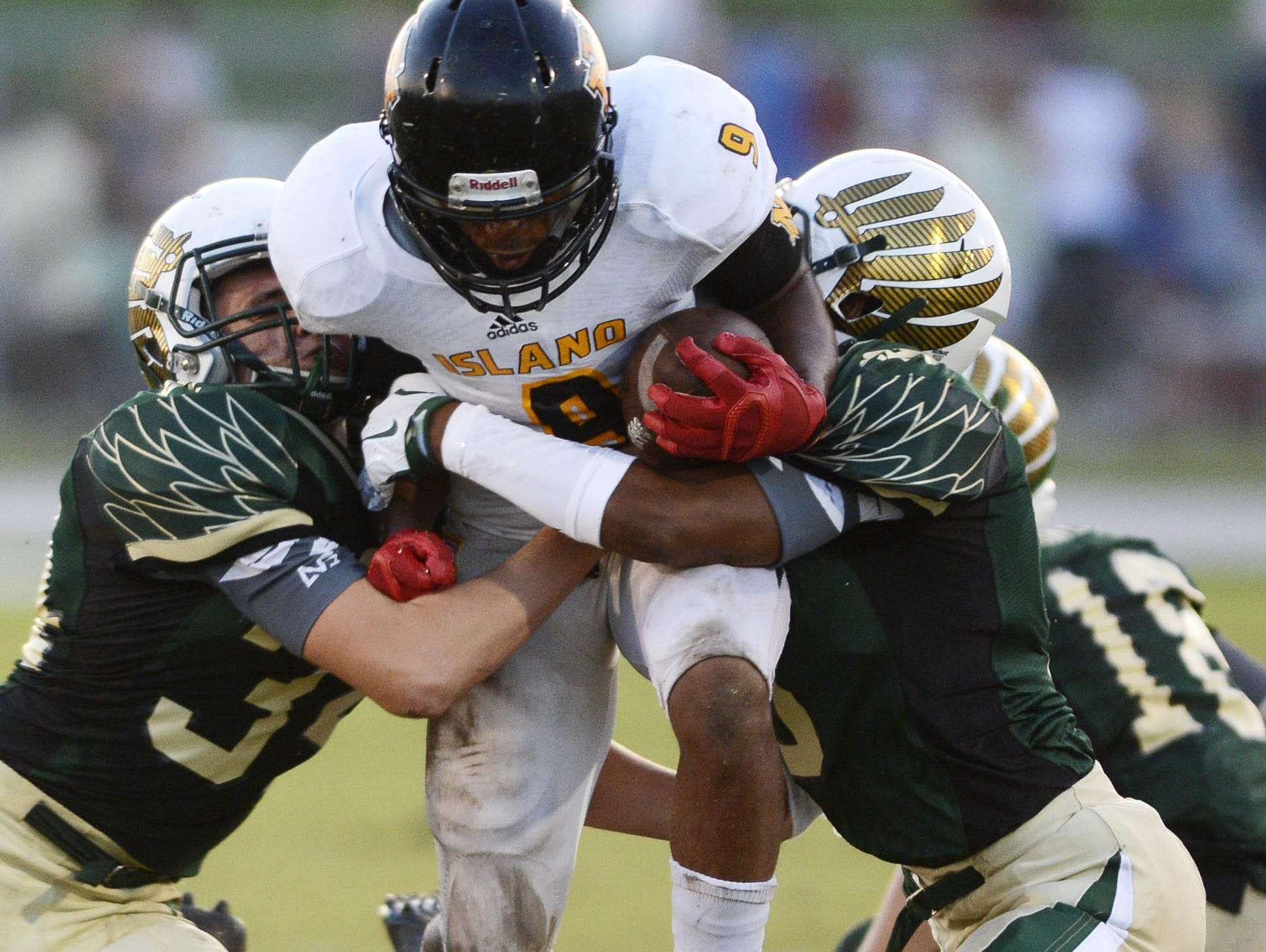 Merritt Island's Taquan Pratt (9) is caught between Viera defenders Brandon Mays (34) and Will Champion (3) during Friday's game at Viera High School.