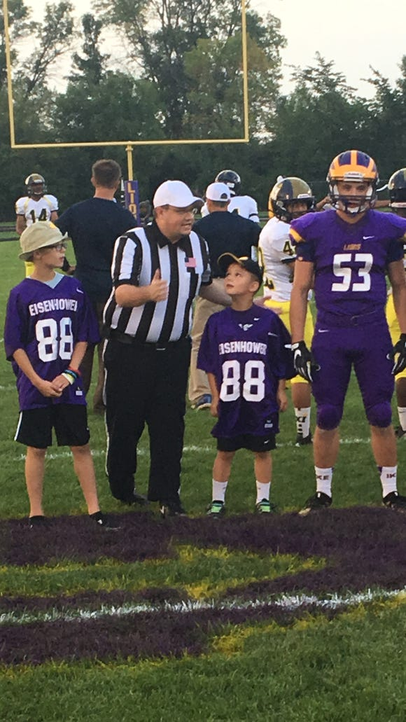 New Berlin Eisenhower's Jaron Radish (53) accompanied by his two younger brothers, Jude and Jaxson, prior to a game against Pius XI on Sept. 9.