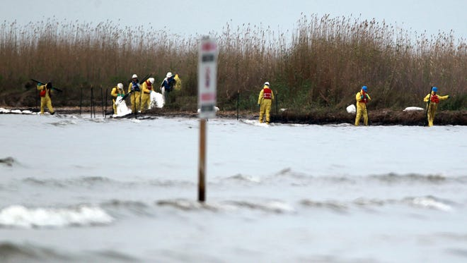 In this March 24, 2014 photo, crews work to clean oil from the shore area in Galveston, Texas. officials said Monday night that changing currents, winds and weather were pushing the oil not only further into the Gulf, but also southwest along Galveston Island, resulting in expanded oil recovery efforts.