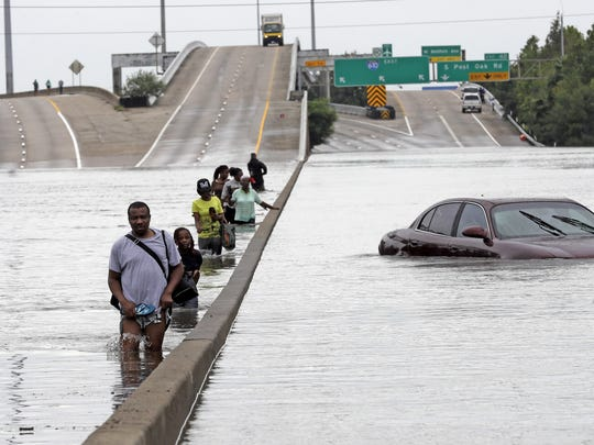 Evacuees wade down a flooded section of Interstate 610 as floodwaters rise Sunday in Houston. The remnants of Hurricane Harvey sent devastating floods pouring into Houston as rising water chased thousands of people to rooftops or higher ground.