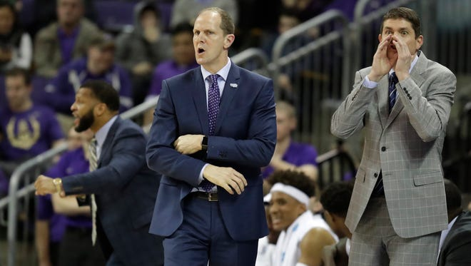 Washington head coach Mike Hopkins, center, along with assistants Will Conroy, left, and Dave Rice, right, has Washington in contention for an NCAA tournament bid.