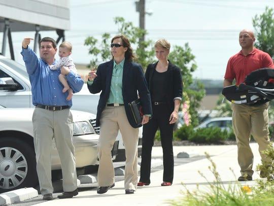 Tanner Harris, SmartBank employee, left, talks to investigators