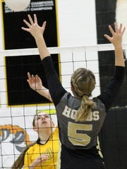 Kristyn Archuleta spikes a ball over Hobbs' Hannah Strickland on Tuesday night at the Tiger Pit.