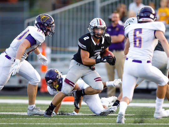 Ankeny Centennial High School's Jensen Gates (2) runs the ball on Johnston in the first half Friday, Aug. 25, 2017, during their game in Ankeny.
