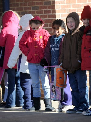 Mike Tripp/The News Leader Dressed for the weather, third-graders brave the cold as they gathered together outside the building that houses their classroom and wait to go in after walking back from the cafeteria following lunch at Hugh K. Cassell Elementary School on Tuesday, Dec. 14, 2010. Along with three other Augusta County elementary schools, the design of Cassell Elementary has students make use of breezeways when traveling from classroom to other buildings like the cafeteria.