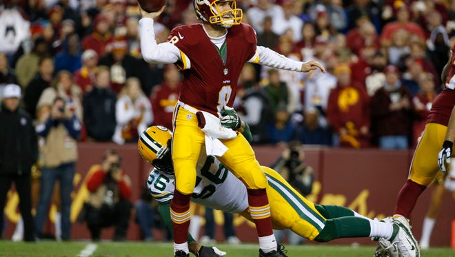 Washington Redskins quarterback Kirk Cousins (8) throws the ball under pressure from Green Bay Packers outside linebacker Julius Peppers  during the first half of Sunday's NFC Wild Card game. Green Bay rolled past Washington, 35-18, setting up a matchup against the Arizona Cardinals next weekend.