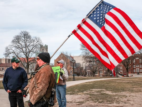 Will Scott from Mason Michigan, attends a pro Second Amendment rally with his flag and his gun at the State Capitol in Lansing, Saturday, March 24, 2018.