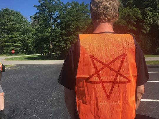 A member of The Satanic Temple Indiana cleans a part