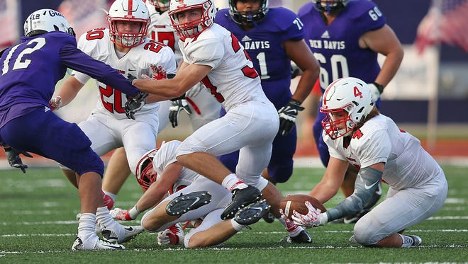 Center Grove Trojans Bailey Bennett (4) goes after a fumble by Ben Davis Giants wide receiver Jermaine Hoskins (12), turning possession over to Center Grove during first quarter action at Ben Davis High School, Friday, September 9, 2016.